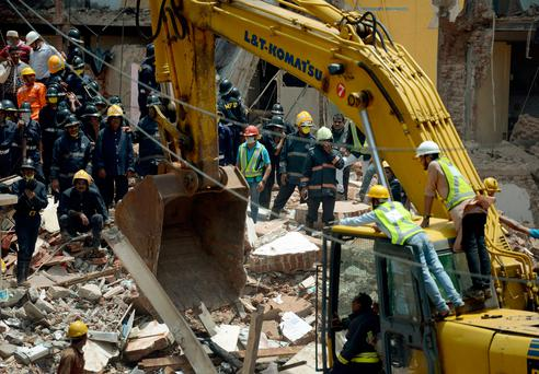 Indian rescue workers look for survivors in the debris of a collapsed building in Mumbai on
