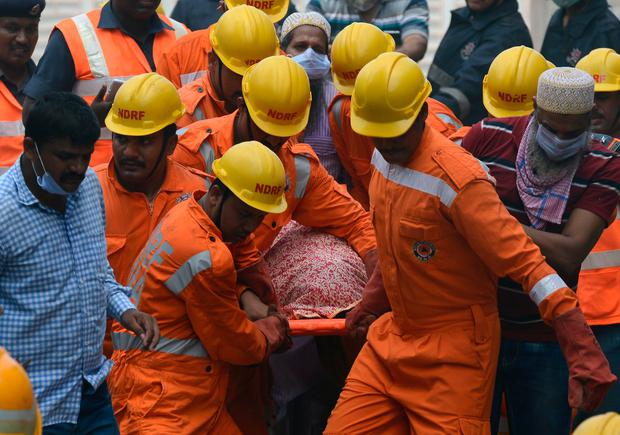 Indian rescue workers carry a victim's body from the building collapse site in Mumbai on