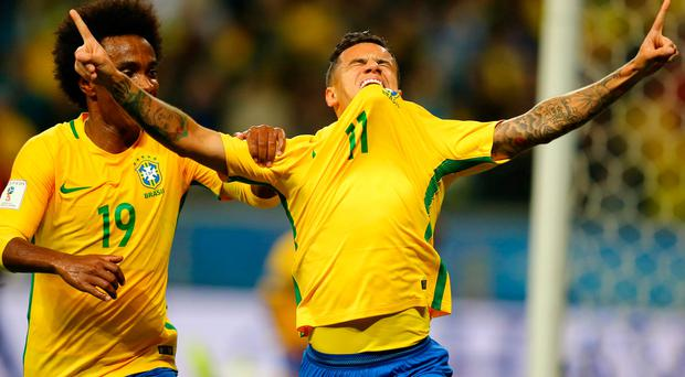 Philippe Coutinho of Brazil celebrates his goal against Ecuador with teammate Willian