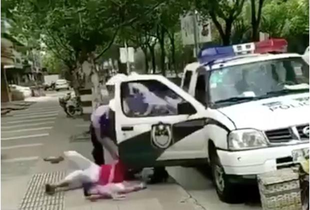 Video shows a policeman throw a woman and child to the ground amid a row over a parking ticket via Twitter