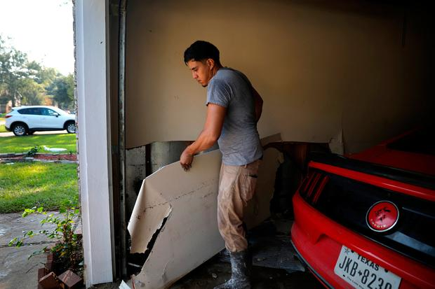 Juan Puente removes part of a wall damaged by Tropical Storm Harvey at his house in East Houston, Texas, U.S. September 1, 2017. REUTERS/Carlos Barria