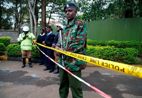 Policemen stand in front of a cordon line following a fire which burnt down one dormitory of Moi Girls school in Nairobi Kenya