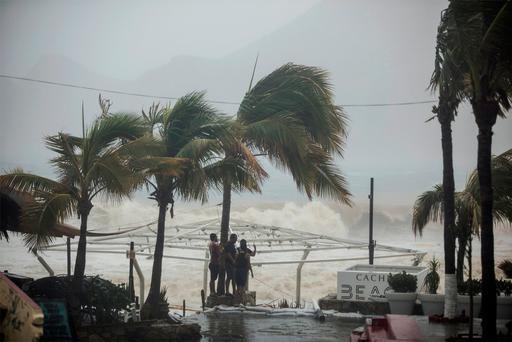 People stand next to swaying palm trees following the passing of Tropical Storm Lidia in Los Cabos, Mexico, August 31, 2017. REUTERS/Fernando Castillo