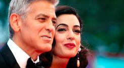 Actor and director George Clooney and his wife Amal pose during a red carpet event for the movie