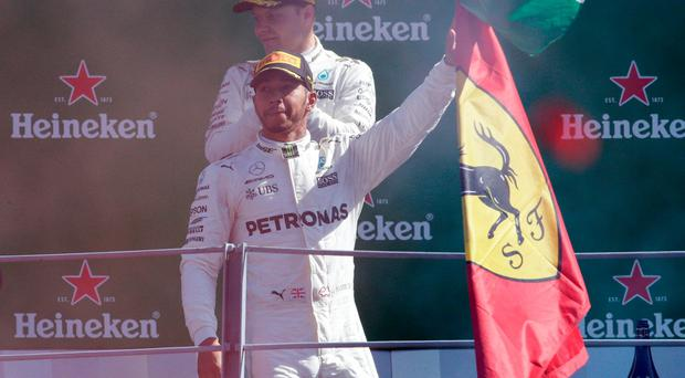 Mercedes' Lewis Hamilton waves to the fans from on the podium as Valtteri Bottas applauds the fans. REUTERS/Max Rossi