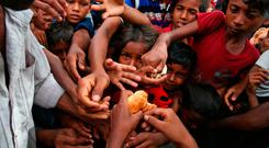 Myanmar's Rohingya Muslim ethnic minority children stretch their hands out to receive food distributed by locals at the Kutupalong makeshift refugee camp. AP Photo/Mushfiqul Alam
