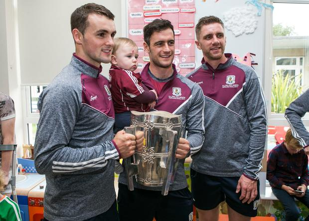 Galway Hurlers Johnny Coen, David Burke and Aidan Harrington with 10 month old Conor Murray from Galway at Crumlin Childrens Hospital. Photo: Kyran O'Brien