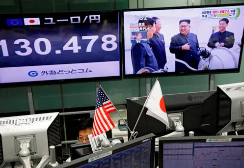 An employee of a foreign exchange trading company works near monitors showing TV news on North Korea's nuclear test (R) in Tokyo, Japan