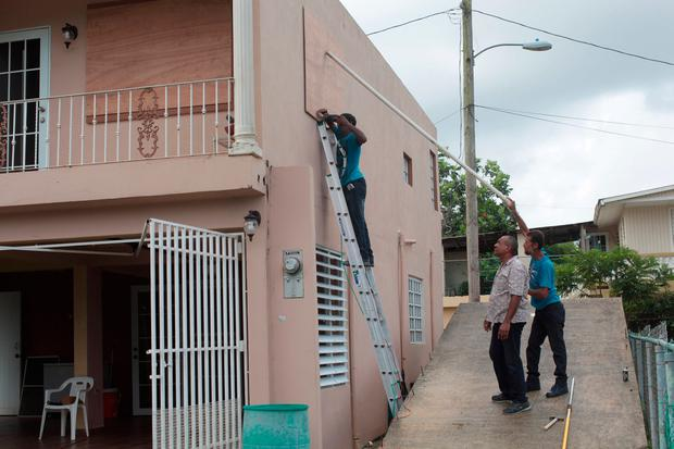 Men cover the window of a house in preparation for Hurricane Irma, in Toa Baja, Puerto Rico September 5, 2017. REUTERS/Alvin Baez