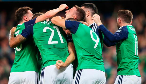 Jonny Evans, here being mobbed by his teammates, received praise from Aaron Hughes after his performance against the Czechs. Photo: PA