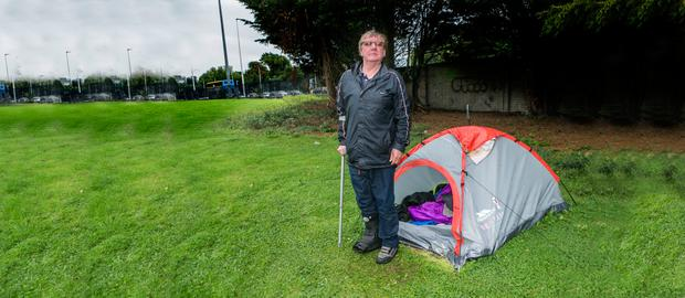 John Keena with the tent he has been sleeping in for around a month on a green overlooking the hotel. Picture: Kyran O'Brien