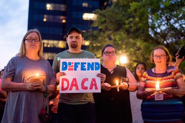 Martha Waggonner, Walker Waggonner, Katie Powell and Gail McGlothin stand in silence holding candles and signs during a silent vigil in honor of Deferred Action for Childhood Arrivals (DACA) at T.B. Butler Fountain Plaza in Tyler, Texas, on Tuesday, Sept. 5, 2017.(Chelsea Purgahn/Tyler Morning Telegraph)