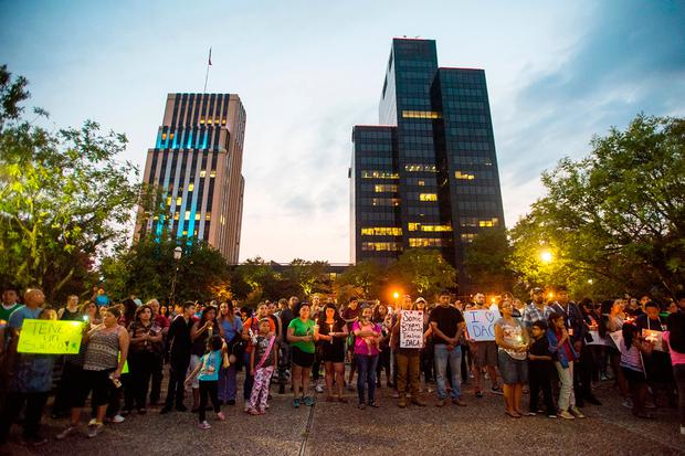 People stand in silence with candles and signs during a silent vigil in honor of Deferred Action for Childhood Arrivals (DACA) at T.B. Butler Fountain Plaza in Tyler, Texas, on Tuesday, Sept. 5, 2017. (Chelsea Purgahn/Tyler Morning Telegraph)