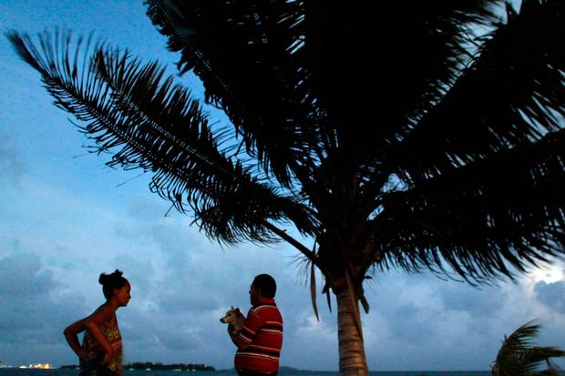 A couple watch the sunset from a seafront as hurricane Irma approaches Puerto Rico in Fajardo on September 5, 2017.