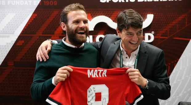 Juan Mata of Manchester United poses on the Molca World stand with a signed shirt during day 2 of the Soccerex Global Convention at Manchester Central Convention Complex