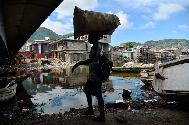 A woman walks next to the Mapou River, in Shadaa neighborhood, in Cap-Haitien, in the north of Haiti, 240 km from Port-au-Prince, ahead of Hurricane Irma on September 5, 2017.