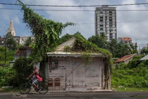 A man rides past a boarded up house as part of preparations ahead of the arrival of Hurricane Irma on September 5, 2017, in the French overseas island of Guadeloupe.