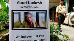 A security guard walks past a placard installed at the Press Club of Kolkata in solidarity with Gauri Lankesh, a senior Indian journalist who according to police was shot dead outside her home on Tuesday by unidentified assailants in southern city of Bengaluru, in Kolkata, India September 6, 2017. REUTERS/Rupak De Chowdhuri