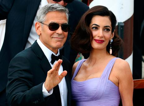 Actor and director George Clooney waves next to his wife Amal as they leave the hotel before the red carpet for the movie Suburbicon at the 74th Venice Film Festival in Venice Italy