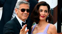 Actor and director George Clooney waves next to his wife Amal as they leave the hotel before the red carpet for the movie Suburbicon at the 74th Venice Film Festival in Venice, Italy September 2, 2017. REUTERS/Alessandro Bianchi