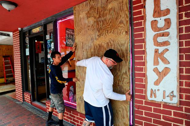 Noel Garcia and Mike Ehlis put plywood over windows of their business as they prepare for Hurricane Irma in Miami. Photo: GETTY