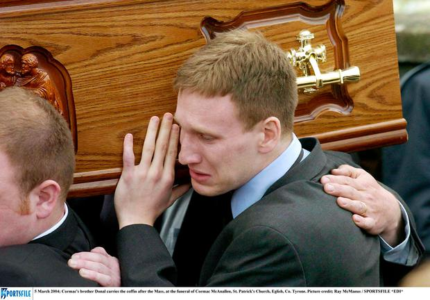 Cormac's brother Donal carries the coffin after the funeral of Cormac McAnallen