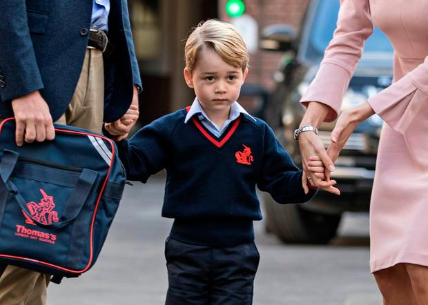 Britain's Prince George (C) accompanied by Britain's Prince William (L), Duke of Cambridge arrives for his first day of school at Thomas's school where he is met by Helen Haslem (R) head of the lower school in southwest London on September 7, 2017. / AFP PHOTO / POOL / RICHARD POHLERICHARD POHLE/AFP/Getty Images