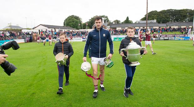 David Burke with Tony Keady's sons Jake and Harry carry Galway's three trophies – senior, minor and Leinster – ahead of a game between the 1988 All-Ireland winning team and this year's winners, held in honour of the late Tribesmen legend in Athenry last night. Photo: Andrew Downes, Xposure