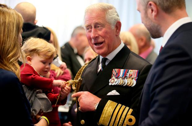 18 month old Imogen Holm pulls the braid on the uniform of the Britain's Prince Charles, at an reception following the naming ceremony of the Royal Navy's new aircraft carrier HMS Prince of Wales at the dockyard in Rosyth, Scotland September 8, 2017. REUTERS/Jane Barlow/Pool