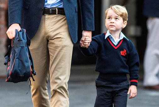 Prince George holds his father Britain's Prince William's hand as he arrives on his first day of school at Thomas's school in Battersea, London, September 7, 2017. REUTERS/Richard Pohle/Pool