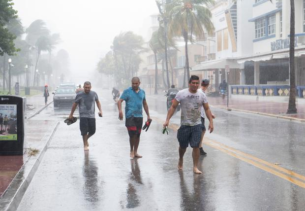People walk down the street as winds and rain begin to hit as outer bands of Hurricane Irma arrive in Miami Beach, Florida, September 9, 2017. Photo: AFP PHOTO / SAUL LOEBSAUL LOEB/AFP/Getty Images