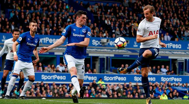 Harry Kane gets in his shot despite the efforts of Michael Keane. Photo: Andrew Yates/Reuters