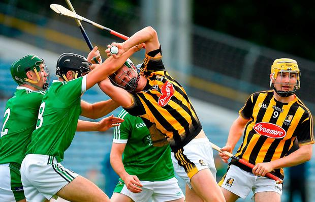 Kilkenny's Alan Murphy is tackled by Limerick's Sean Finn, left, and Colin Ryan. Photo by Brendan Moran/Sportsfile