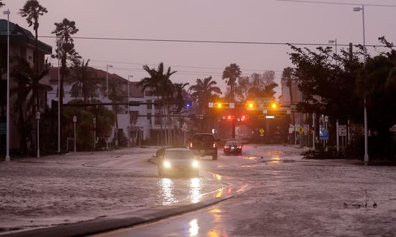 Vehicles drive through a flooded street as Hurricane Irma passes through Naples, Fla., Sunday, Sept. 10, 2017. (AP Photo/David Goldman)