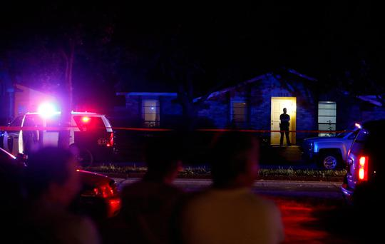 Onlookers watch police work the scene of a shooting at a home in Plano, north of Dallas, Texas, Sunday. (Vernon Bryant/The Dallas Morning News via AP)
