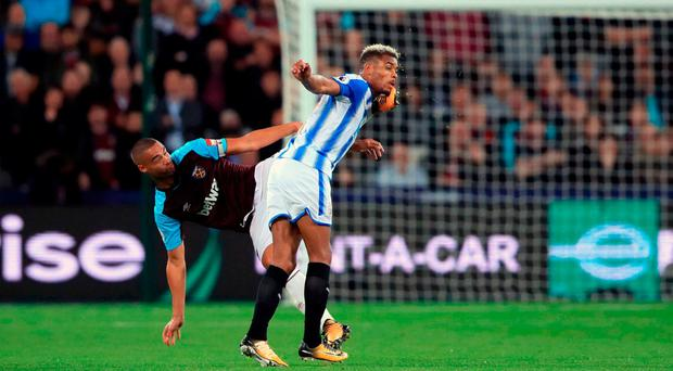 West Ham United's Winston Reid (left) and Huddersfield Town's Steve Mounie battle for the ball during the Premier League match at the London Stadium.