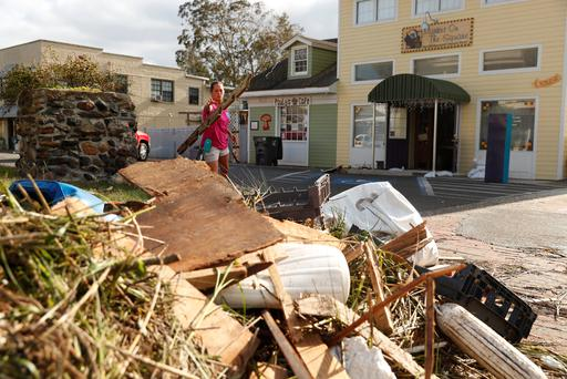 A resident tosses a piece of debris as she works to clear the street after Hurricane Irma passed through in St Marys, Georgia