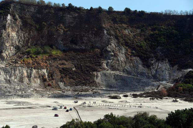 Rescuers stand on the site where three people reportedly died when they fell into a crater in a steamy volcanic field in Pozzuoli, near Naples, Italy. Photo: AP