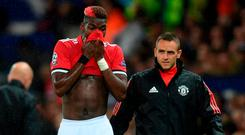 Paul Pogba of ManchesterUnited reacts to being forced off through injury during the UEFA Champions League Group A match between Manchester United and FC Basel at Old Trafford