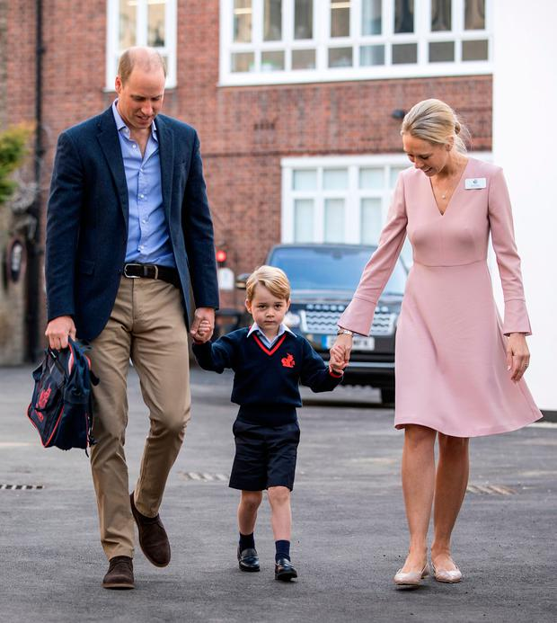Prince George holding hands with the Duke of Cambridge and Helen Haslem, head of the lower school, at Thomas's Battersea in London, as he started his first day of school. Photo: Richard Pohle/The Times/PA Wire