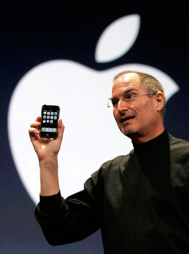 The then Apple CEO – Steve Jobs – holds up the first iPhone during his keynote address at MacWorld Conference & Expo in San Francisco in 2007. Photo: AP