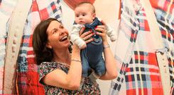 Finn Keenaghan (two months) and Ann Murphy in front of a portrait of her father Tadhg Devane on the streets of Portmagee in Co Kerry at the launch of the National Library 'Photo Detectives' exhibition. Photo: Collins