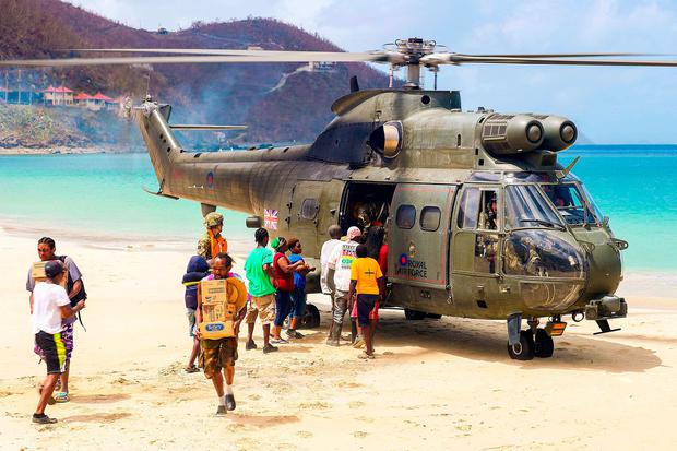 RAF Puma helicopter of 33 Squadron on the beach of Cane Garden Bay delivers essential aid to residents in Tortola, the largest of the British Virgin Islands. Photo: PA Wire