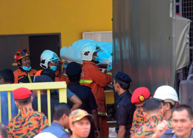 Bodies are carries out by rescue personnel from an Islamic religious school after firefighters put out a fire on the outskirts of Kuala Lumpur Thursday, Sept. 14, 2017. (AP Photo)