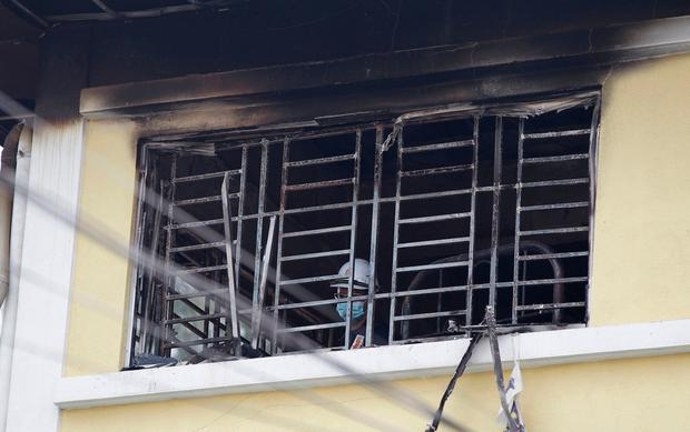Forensic police officer investigates burnt windows at an Islamic religious school following a fire on the outskirts of Kuala Lumpur Thursday, Sept. 14, 2017. (AP Photo/Daniel Chan)