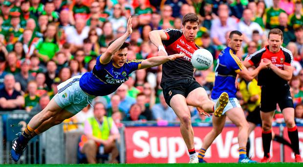 Mayo's Lee Keegan gets his shot away despite the efforts of Kerry's Paul Murphy during their semi-final battle. Photo: RAMSEY CARDY/SPORTSFILE