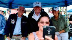 US President Donald Trump (centre), Vice President Mike Pence and First Lady Melania Trump pose for a selfie as they help serve food to some of the people affected by Hurricane Irma. Photo: Getty Images