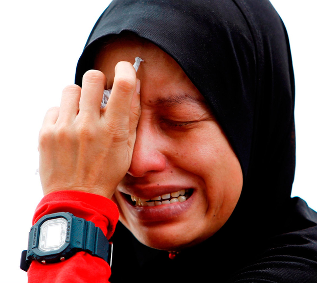 Nadia Azalan, whose brother lost his life in the fire at the school, reacts to the tragedy. Photo: Reuters/Lai Seng Sin