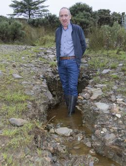 Henry O'Donnell stands in one of the craters on a road leading to his farm, caused by the massive flood waters on the hills around Inishowen. (North West Newspix)