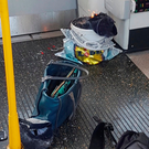 Personal belongings and a bucket with an item on fire inside it, are seen on the floor of the carriage. Photo: Reuters